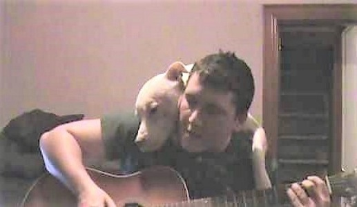 video of a man singing a song to his dog